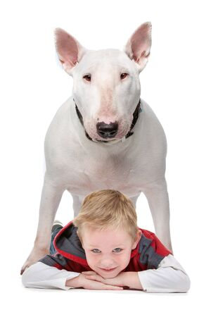 A little boy lying on the floor with his dog standing above him photo