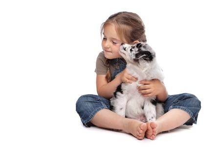 little girl and a puppy in front of a white background Stock Photo