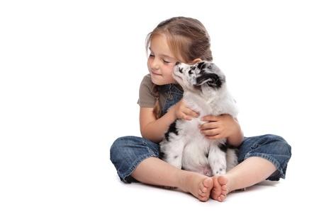 puppy love: ni�a y un cachorro delante de un fondo blanco