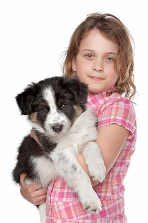 Girl and border collie puppy in front of white background