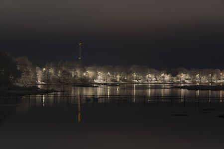 weir: fish weir and snow covered trees, river at night