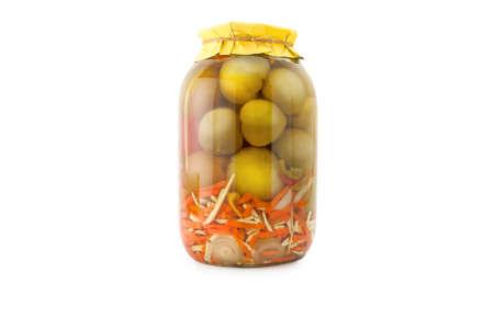 cebollas: Caseras en vinagre los tomates verdes con zanahorias y cebollas en frasco de vidrio con envoltura de papel amarillo. conservas caseras, encurtidos. Tarro de tomates marinados verdes enlatados aislado en blanco