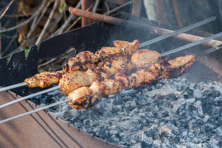 chargrill: Strung meat on skewers roasted on hot coals. Cooking pork shashlik on skewer, in brazier outdoors. Browned pieces of meat vyalyatsya on hot coals, close-up.