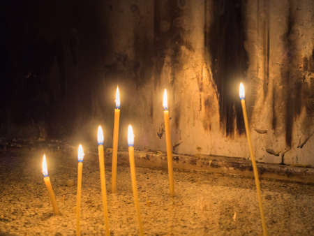 sooty: Picture of the several wax candles lighted in a dark room in a church. Candles lighting against background of the sooty white wall. Stock Photo