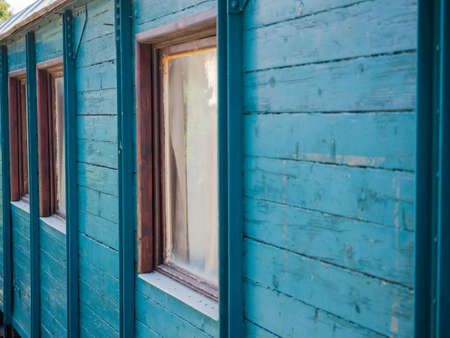 planking: Picture of the wooden wall painted with turquoise blue colour. Old paintwork on the wall. An old country house made of planking. Brown window frames in the wooden country house.