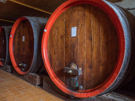 planking: Picture of a brown wine barrels stacked in the old cellar of the winery. Background of the wooden barrels made of brown planking. Stock Photo