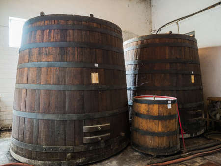 planking: Picture of a three brown wine barrels stacked in the old cellar of the winery. Background of the wooden barrels made of brown planking. Stock Photo