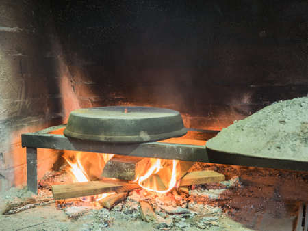 sooty: Picture of the stone bread oven stove with burning wood fire and red flames inside. Image of the burning wood fire against the background of the sooty wall. Stock Photo