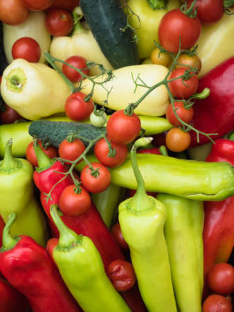 consuming: Background of the assorted raw organic vegetables. Red, green and yellow peppers with red tomato and green cucumbers.
