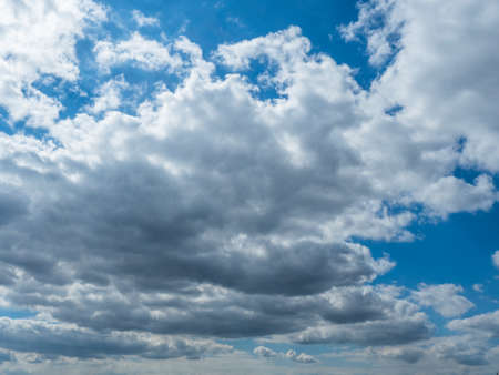 View of the cloudy sky from the ground. Picture of the blue sky with beautiful white clouds.