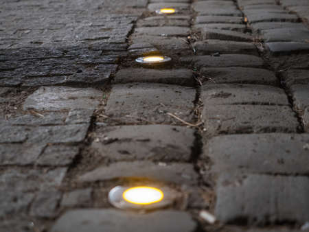 cobblestone road: Picture of the cobblestone paved road with spotlight close up. Dark brown cobblestone road pattern close up. Selective focus on the middle of the picture. Spotlights against the blurred background.