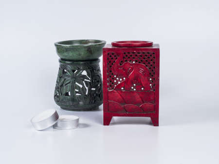 Picture of a red aroma lamp with two candles on white background. Aroma lamp made of stone. Elephant carved on aroma lamp.