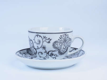 Close up on white tea cup decorated with designs standing on a saucer isolated on white background. Side view. Stock Photo
