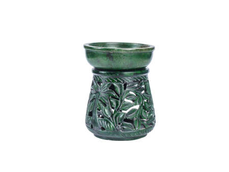 Picture of a green aroma lamp made of stone isolated on white background. Made of stone aroma lamp with floral ornaments. Stock Photo