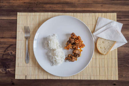 carnes y verduras: Scene with snow white ceramic dish of rice and roast meat, stew, meats with vegetables on a bamboo napkin on a wooden table from the old boards. Slices of white bread on the white paper napkins