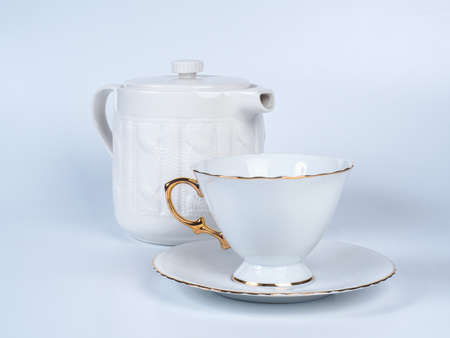 Picture of the white infuser teapot near tea cup decorated witn white and golden colour. Infuser teapot and tea cup standing on a saucer on white background.