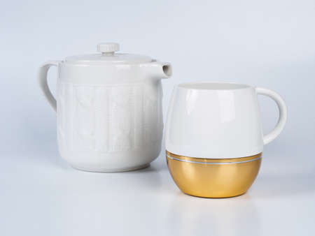Picture of the white infuser teapot near tea cup decorated witn white and golden colour. Infuser teapot and tea cup on white background. Stock Photo