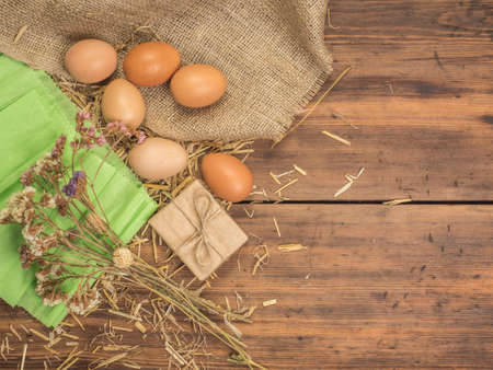 sackcloth: Rural creative background with brown eggs, burlap, straw, green paper and dry flowers on wooden table from old planks. Vintage, rustic background for Easter postcards, restaurant menus or advertising