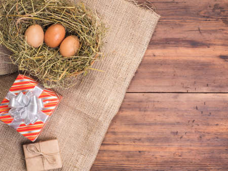 useful: Rural eco background with brown chicken eggs, gift box and straw on the background of old wooden planks. The view from the top. Creative background for Easter cards, menu or advertising Stock Photo