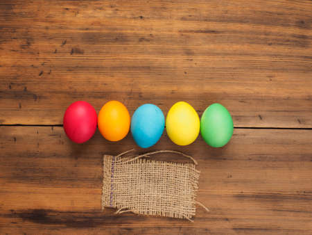 Easter eggs on old brown wood and burlap background. Top view, horizontal. Mock up for your greetings card or poster. Russian and Ukrainian, orthodox, slavic traditional Easter, rural background. Stock Photo