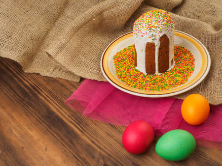 Easter cake, ceramic bowl with colorful sweet powder and easter colored egg. Russian and Ukrainian, orthodox slavic traditional Easter kulich on rural background. Old wood, red mesh paper and burlap. Stock Photo