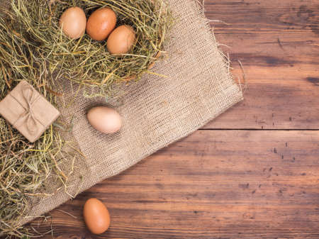 wood texture: Rural eco background with brown chicken eggs, gift box and straw on the background of old wooden planks. The view from the top. Creative background for Easter cards, menu or advertising Stock Photo