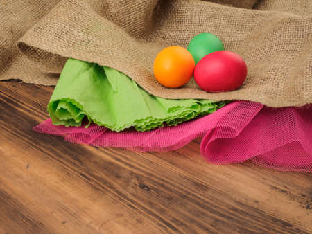 Easter colored egg, burlap, crinkled green paper and a red grid on a brown background from old wood, rural table. Russian and Ukrainian, orthodox, slavic traditional Easte. Stock Photo