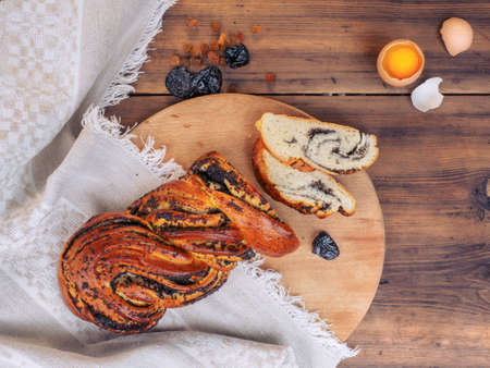 homemade bread: Cut sweet twisted bun with poppy seeds. Still life in rustic style, illustration for Breakfast, cover for menu. Top view composition with raisins, prunes and egg on a background of old wood and cloth Stock Photo