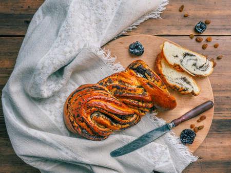 Snij een zoet, verdraaid broodje met maanzaad. Samenstelling met rozijnen, pruimen op een achtergrond van oud hout, doek en mes. Hoogste mening voor uitstekend stilleven in rustieke stijl, illustratie voor Ontbijt.