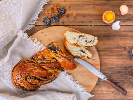 Cut sweet twisted bun with poppy seeds. Composition with raisins, prunes and egg on a background of old wood, cloth and knife. Vintage still life in rustic style, illustration for Breakfast. Top view.