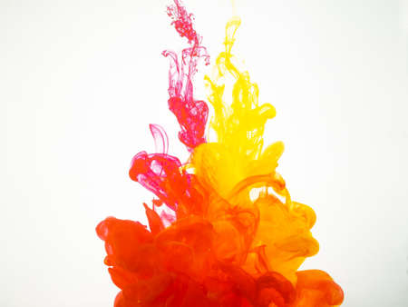 Movement of acrylic colours in water photographed while in motion. Abstract swirling of ink in water. Splash of ink isolated on white background. Yellow-red acrylic colour dissipation