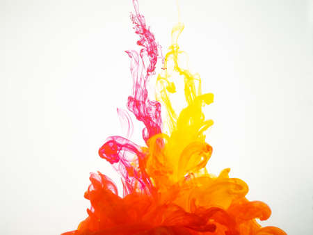 Image of two droplets of ink mixing under water. Colours dropped into liquid and photographed while in motion. Ink splash isolated on white background. Abstract background