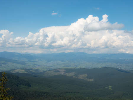 Landscape of mountains and cloudy sky. Carpathians mountains, west Ukraine. Big white cumulus flowing in blue sky. Ukrainian nature background. Green hillsides at summer. Blurred background 版權商用圖片