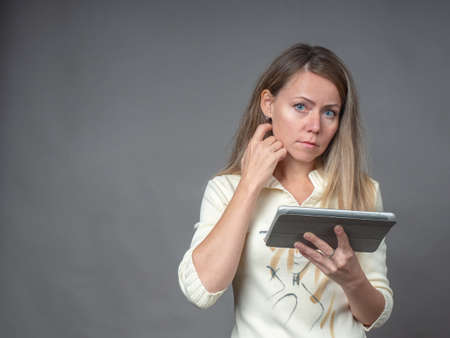 Portrait of european woman with tablet isolated on gray background. Attractive thoughtful woman looking in camera. Businesswoman working online on mobile computer, do shopping in online store