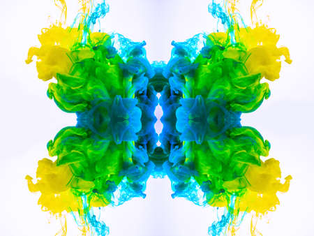 Abstract background with yellow-blue-green mystic clouds, swirling fog. Macro shot of acrylic ink blending in liquid. Colorful abstract shapes, cephalopod ink isolated on white background