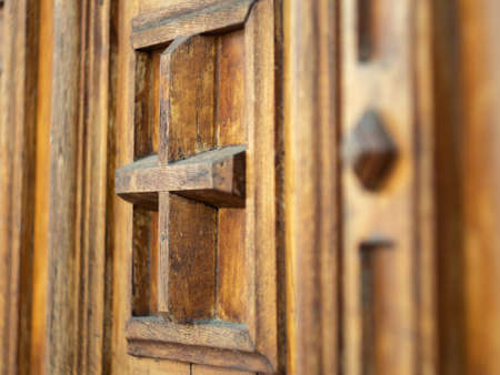 Fragment of brown wooden door in monastery, close up view. Door with cross and decorative carvings. Ancient wooden door in monastery, Ukraine. Ornate gate. Blurred background. Selective soft focus Stockfoto
