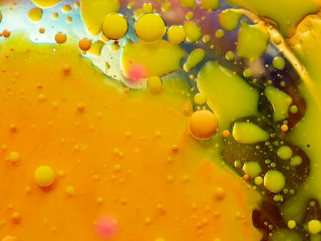 Yellow and orange bubbles with spots of green paint, abstract background. Close up macro shot. Blurred background. Selective soft focus. Universe of paint splashes, abstract pattern Banco de Imagens