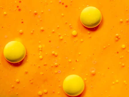 Three yellow spheres on orange background. Close up macro shot. Blurred background. Selective soft focus. Orange universe, an abstract background. Scores of big and small bubbles, abstract pattern Standard-Bild - 120476527