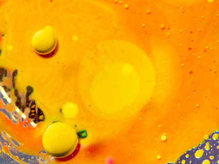 Pattern of yellow abstract orange universe. Close up macro shot. Blurred background. Selective soft focus. Two big yellow spheres and scores of small bubbles. Abstract orange background