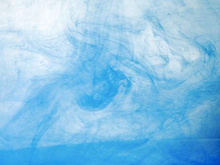 Encre acrylique bleue se dissolvant dans l'eau, vue rapprochée. Arrière-plan flou. Nuages de lumière acrylique se déplaçant dans un fond liquide et abstrait. Peinture bleue se mélangeant à de l'eau, motif abstrait