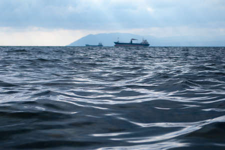 Close up view on sea surface. Two ships sailing on horizon. Sky covered with dense clouds. Water surface is rippling. Selective soft focus. Blurred background