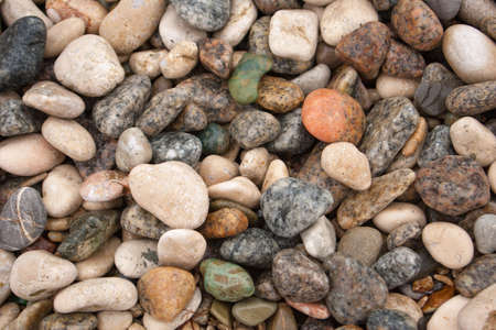 Seashore with gravel stone in summer, close up view. Texture of jackstone. Multicolour pebbles, abstract background