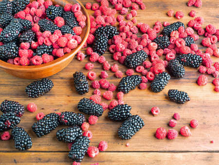 Fresh juicy berries piled on brown table, close up view. Brown bowl full of ripe red raspberries and black mulberries. Texture of wooden desk. Selective soft focus. Blurred background Standard-Bild