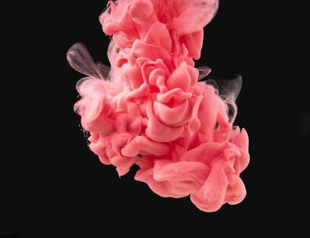 Gota de pintura rosa-roja hace coloridos remolinos bajo el agua, aislado sobre fondo negro, vista de cerca. Tinta que se disuelve en agua. Fondo abstracto para diseño de superposiciones, capa de modo de fusión de pantalla