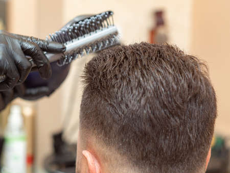 Making modern hairdo with round comb and hair dryer, close up view. Stylists hands in black rubber gloves. Males nape and beige interior of barbershop. Selective soft focus. Blurred background