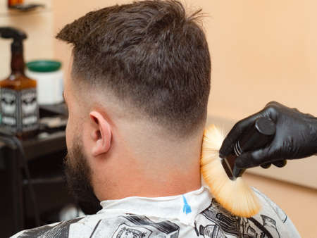 Male visiting hairdressing saloon, close up view. Stylist cutting hair with clipper. Masters hands in black rubber gloves. Interior of barbershop. Selective soft focus. Blurred background