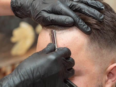 Stylist shaving clients forehead with open razor in barbershop, close up view. Hands in black rubber gloves with open razor. Photographed in barbershop. Selective soft focus. Blurred background Фото со стока