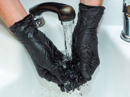 Stylist washing hands in washstand, close up view. Stylists hands in black rubber gloves. Photographed in barbershop. Selective soft focus. Blurred background Stock Photo