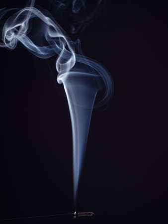 Burning incense with white smoke, isolated on black background, close up view. Structure of white smoke, brush effect. Abstract background. Eastern fragrance for meditation and relaxation
