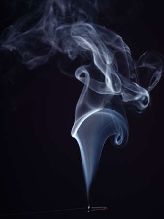 Close up view on white smoke from burning aromatic stick, isolated on black background. Structure of smoke, brush effect. Abstract background. Eastern smell for meditation and relaxation 版權商用圖片